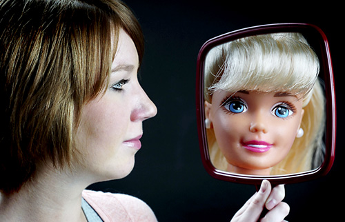 Kids and Body Image - Girl looking in the mirror at Barbie