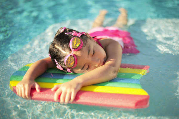 pool safety - girl swimming on swim board